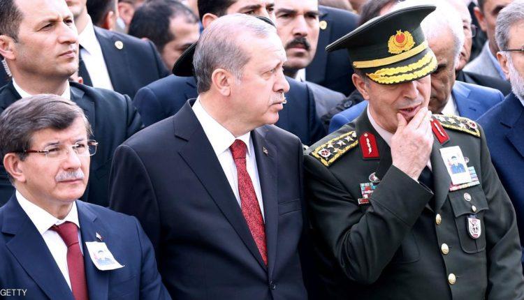 الرئيس التركي رجب طيب أردوغان يتوسط رئيس الوزراء أحمد داوود أوغلو (يسار) وقائد القوات البرية هولوسي أكار (يمين)