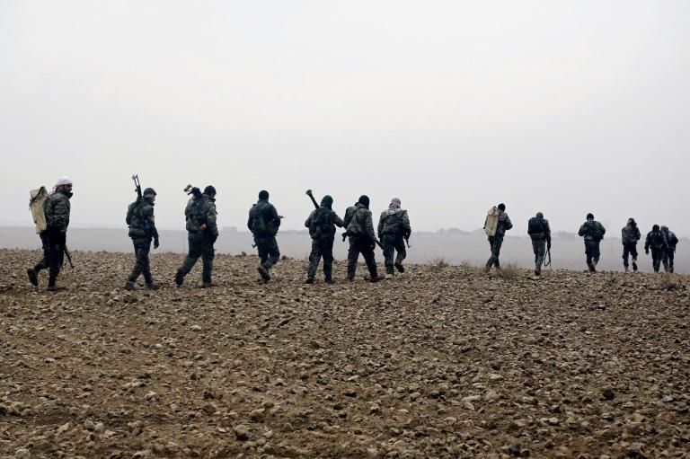 مقاتلون من قوات سوريا الديموقراطية يعبرون احدى القرى في الريف الغربي للرقة