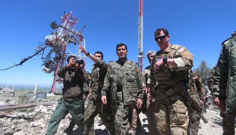 جنود أميركيون ومقاتلون أكراد يتفقدون الموقع المستهدف.