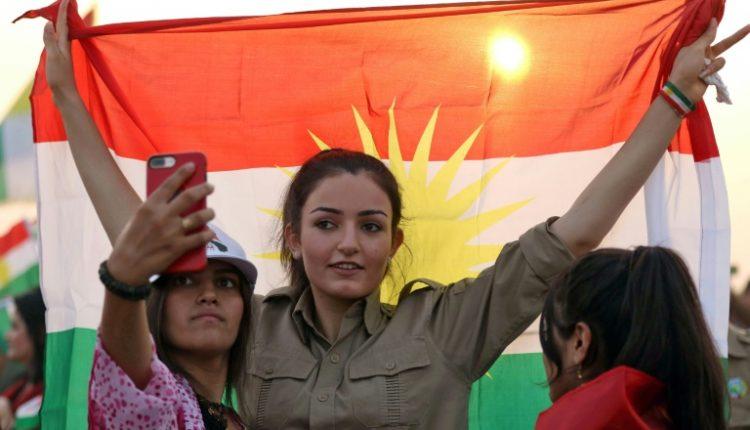 فتيات يلتقطنا صورة مع العلم الكردي