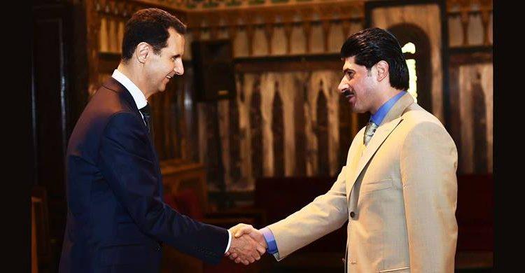 حسام قاطرجي وهو يصافح الأسد