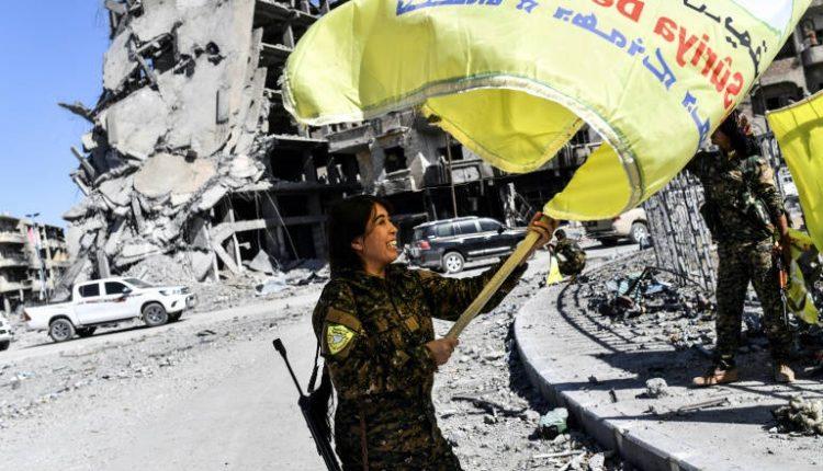 روجدا فلات القيادية في قوات سوريا الديموقراطية ترفع علم هذه القوات في دوار النعيم في الرقة في 17 تشرين الاول/اكتوبر.